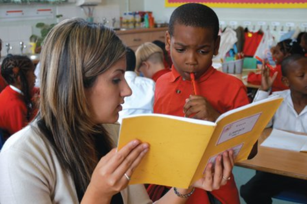 Teacher with student looking at book