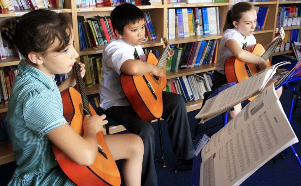 Children playing guitar in music lesson.