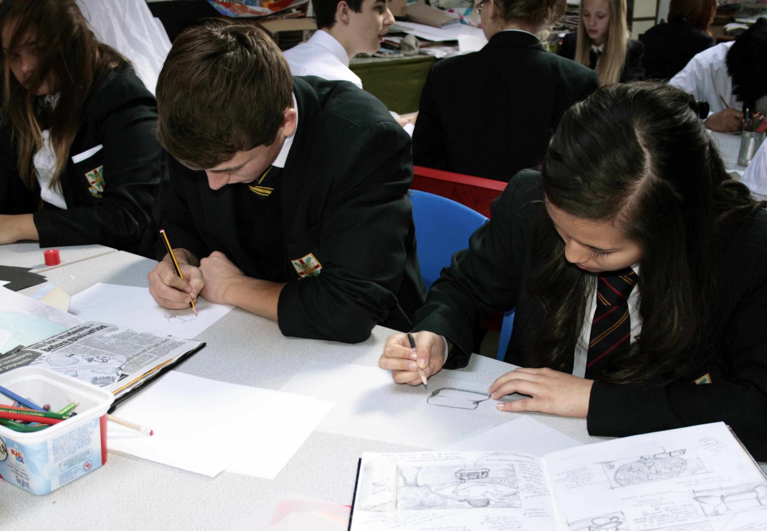 Children writing in work books in class.