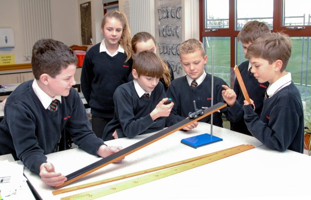 Pupils doing a physics experiment with a slope and wheeled toy.