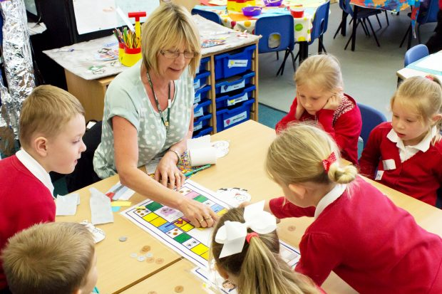 Female teacher sat at a table with primary school pupils explaining a piece of work.
