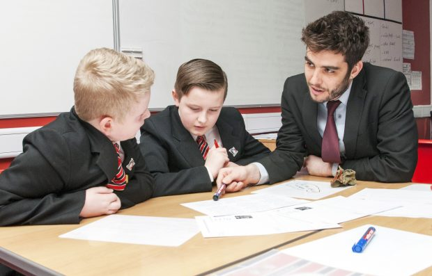 Teacher explaining a point to two pupils at secondary school.
