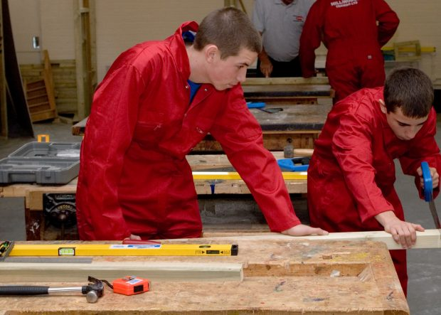 Two apprentices concentrate on sawing a piece of wood
