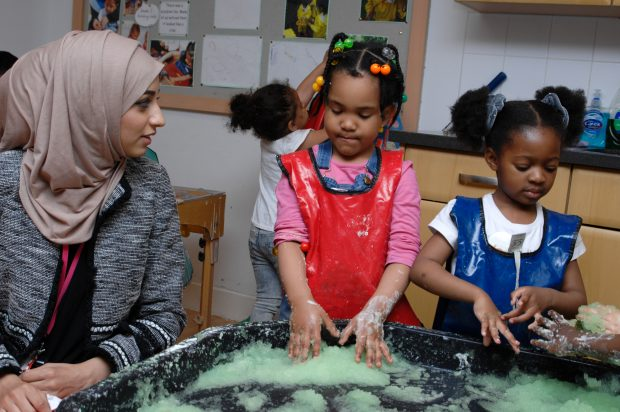 Children doing messy play while an early years staff member looks on.