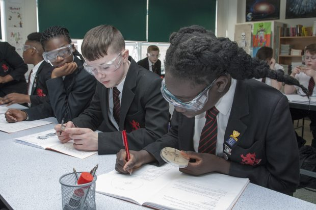 Pupils wearing safety goggles in a classroom.