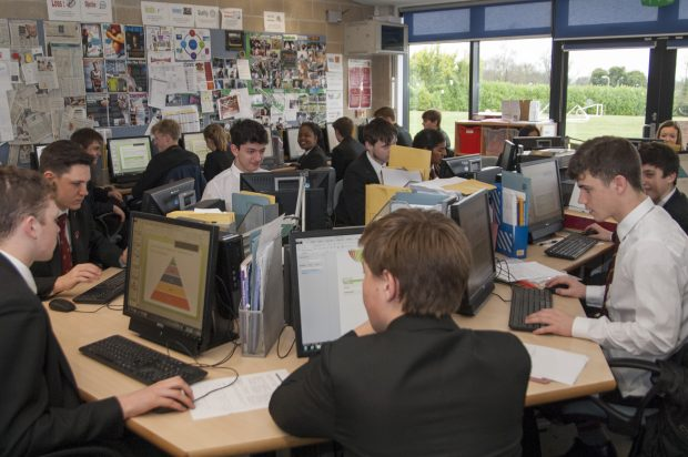 A classroom with pupils looking at graphs on computers.