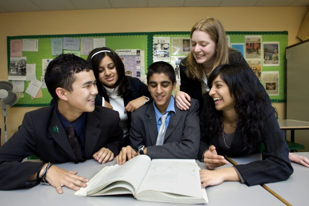 Pupils in a school looking at a large notebook.