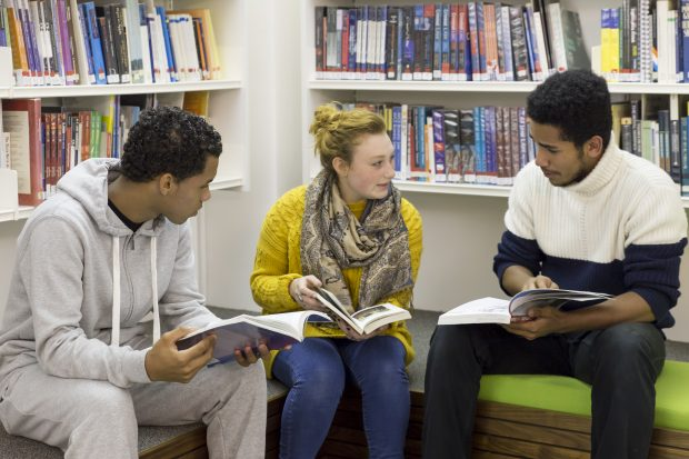 Young people in a library discussing their books.