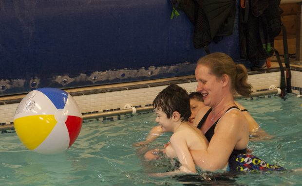 Little boy in the pool with their teacher with the teacher supporting the boy to play with a floating ball