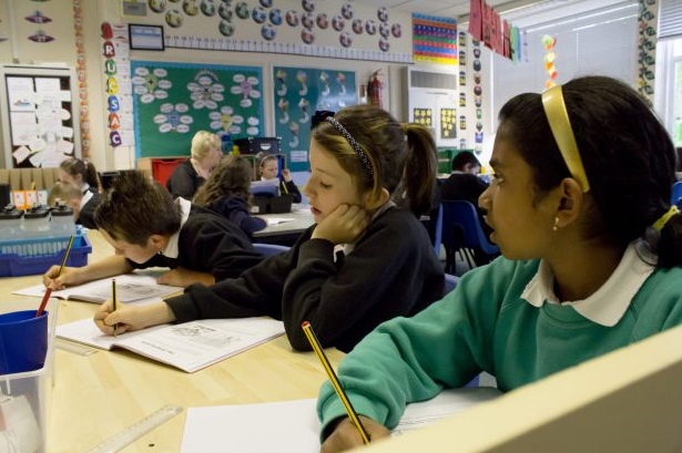 Children sat in a classroom writing in workbooks.