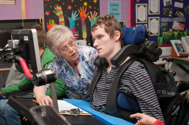 Teenager in a wheelcheer uses a computer with a teacher sat alongside him.