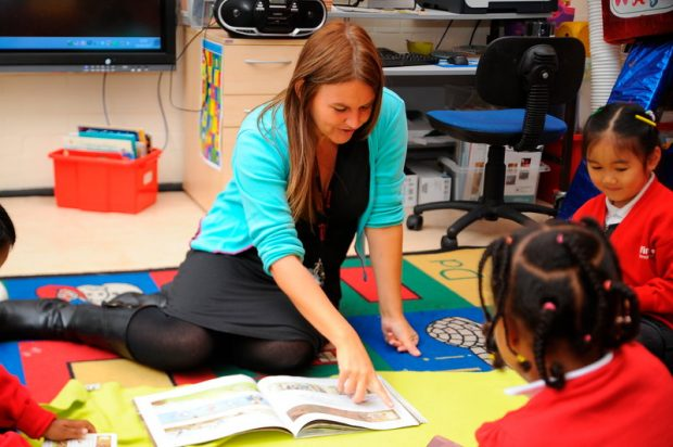Teacher reading to a class of primary school pupils