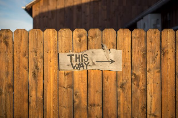 Wooden fence with sign that says 'this way' with an arrow
