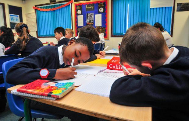 Primary school children writing in books