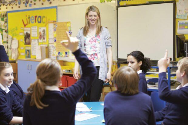 Teacher smiling, teaching a primary school class